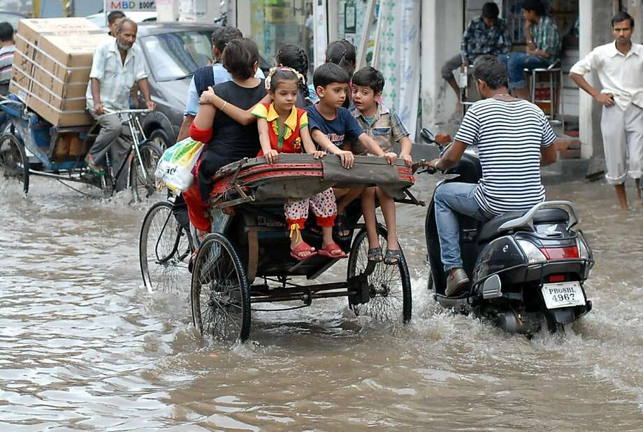 Indian commuters make their way through a waterlogged street after heavy monsoon rains fell in Jalandhar on July 9, 2013.   Authorities have raised to 5,500 the estimated number of people who perished in devastating floods that swept the northern Indian state of Uttarakhand last month.  AFP PHOTO/SHAMMI MEHRASHAMMI MEHRA/AFP/Getty Images Photo: Shammi Mehra, AFP/Getty Images