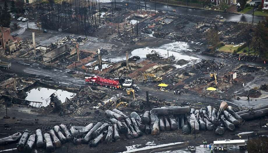 Workers comb through debris Tuesday, July 9, 2013, after a train derailed Saturday causing explosions of railway cars carrying crude oil in Lac-Megantic, Quebec. (AP Photo/The Canadian Press, Paul Chiasson) Photo: Paul Chiasson, Associated Press