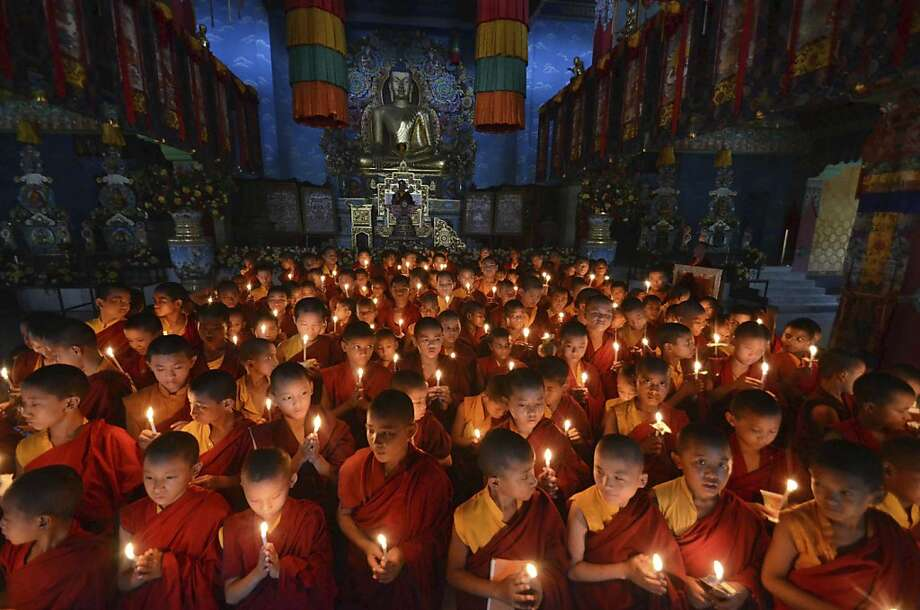 Novice Buddhist monks offer prayers for peace at the Tergar Monastery, the site of an explosion, in Bodh Gaya, about 130 kilometers (80 miles) south of Patna, the capital of the eastern Indian state of Bihar, Tuesday, July 9, 2013. One man has been detained and sketches of two others have been prepared as investigators searched for clues Monday into a series of blasts at some of Buddhism's holiest sites in Bodhgaya. (AP Photo/Manish Bhandari) Photo: Manish Bhandari, Associated Press