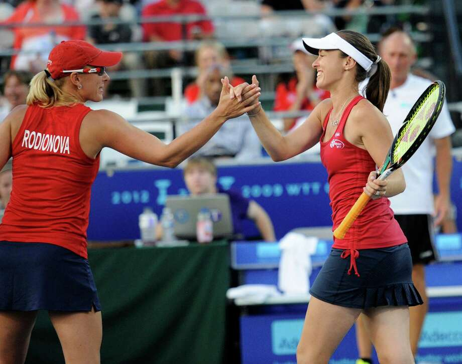 Washington Kastles' Martina Hingis, right, of Switzerland, reacts with Anastasia Rodionova, of Russia, after they won a women's doubles World Team Tennis match against the Boston Lobsters' Katalin Marosi and Jill Craybas, Tuesday, July 9, 2013, in Washington. (AP Photo/Nick Wass) ORG XMIT: DCNW105 Photo: Nick Wass / FR67404 AP