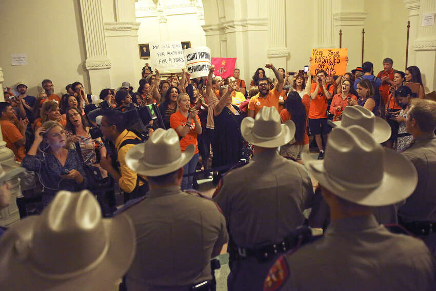 Abortion-rights advocates chant outside the House chamber after state representatives voted 98-49 to give the initial OK to House Bill 2, which would ban abortion at 20 weeks and impose stricter standards for clinics.