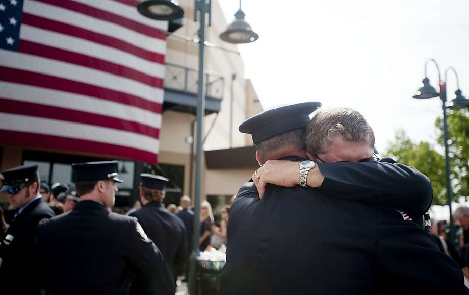PRESCOTT VALLEY, AZ-JULY 9: Chaplain Bob Ossler (R) with the Mayer, Arizona fire department hugs people at the entrance to a memorial service honoring the 19 firefighters killed in a wildfire at Tim's Toyota Center July 9, 2013 in Prescott Valley, Arizona. The firefighters, of the Granite Mountain Hotshots crew, died battling the fast-moving blaze on June 30. (Photo by Laura Segall/Getty Images) Photo: Laura Segall, Getty Images
