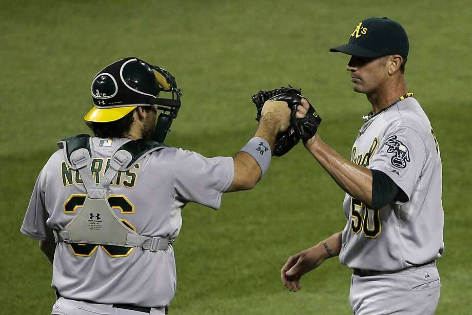 Oakland Athletics closer Grant Balfour (50) celebrates with catcher Derek Norris after getting the final out in the ninth inning of a baseball game against the Pittsburgh Pirates in Pittsburgh Tuesday, July 9, 2013. The Athletics won 2-1. (AP Photo/Gene J. Puskar) Photo: Gene J. Puskar, Associated Press