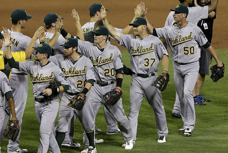 The Oakland Athletics celebrate after a 2-1 win over the Pittsburgh Pirates in a baseball game in Pittsburgh Tuesday, July 9, 2013. (AP Photo/Gene J. Puskar) Photo: Gene J. Puskar, Associated Press