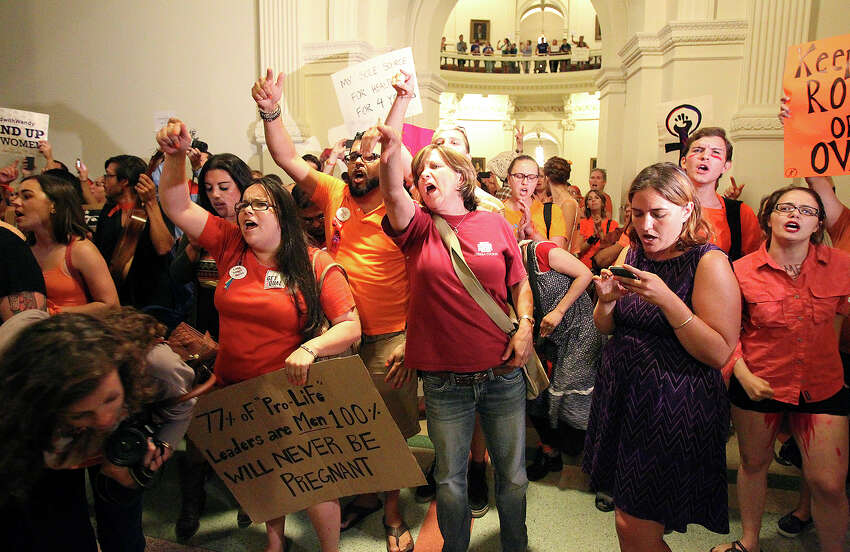 A crowd protests outside the House chamber after the House of Representatives passed abortion legislation on July 9, 2013.