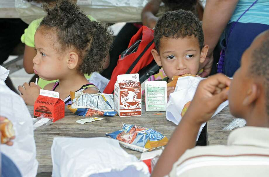 From left, Janai Benedict, 4, and her brother Jaden Benedict, 3, of Schenectady enjoy a free lunch at Jerry Burrell Park on Tuesday, July 9, 2013 in Schenectady, N.Y. Schenectady Inner City Ministry (SICM) and the Campus Kitchens at Union College provide the children with free lunches in various locations in Schenectady during the summer. (Lori Van Buren / Times Union) Photo: Lori Van Buren / 10022868A