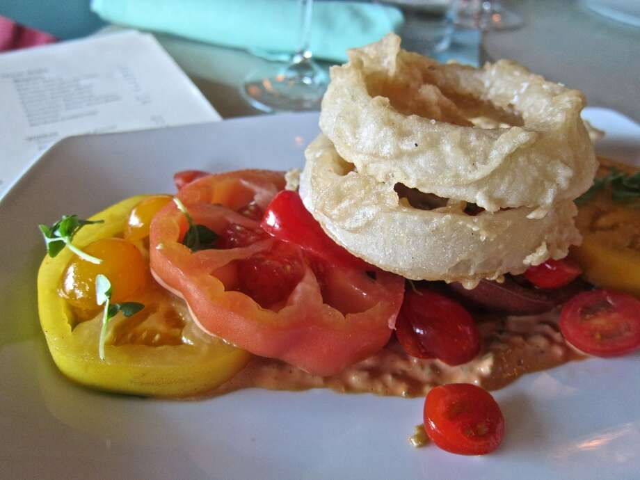The beefsteak tomato salad with Russian dressing and onion rings at Reef is the perfect summer treat. Photo: Alison Cook