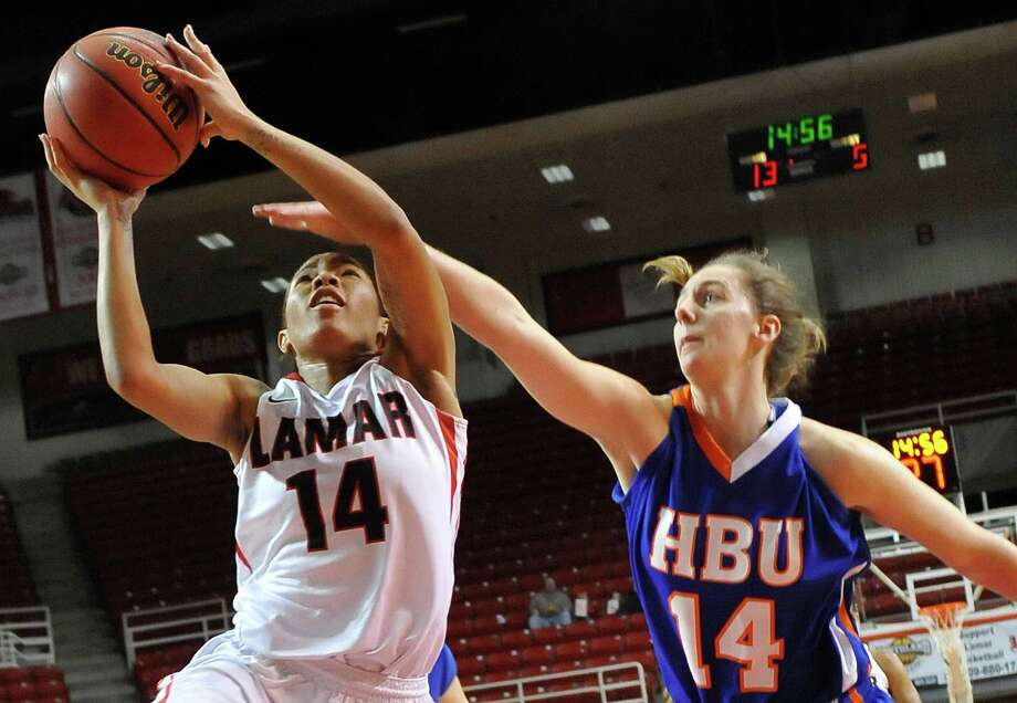 Lady Card #14, Carenn Baylor, left, takes her shot even as Lady Huskie #14, Erin McGarrachan, right, tries to block her view.  The Lamar University Lady Cardinals hosted the Houston Baptist University Huskies Wednesday February 13, 2013 in the Montagne Center.  Dave Ryan/The Enterprise Photo: Dave Ryan