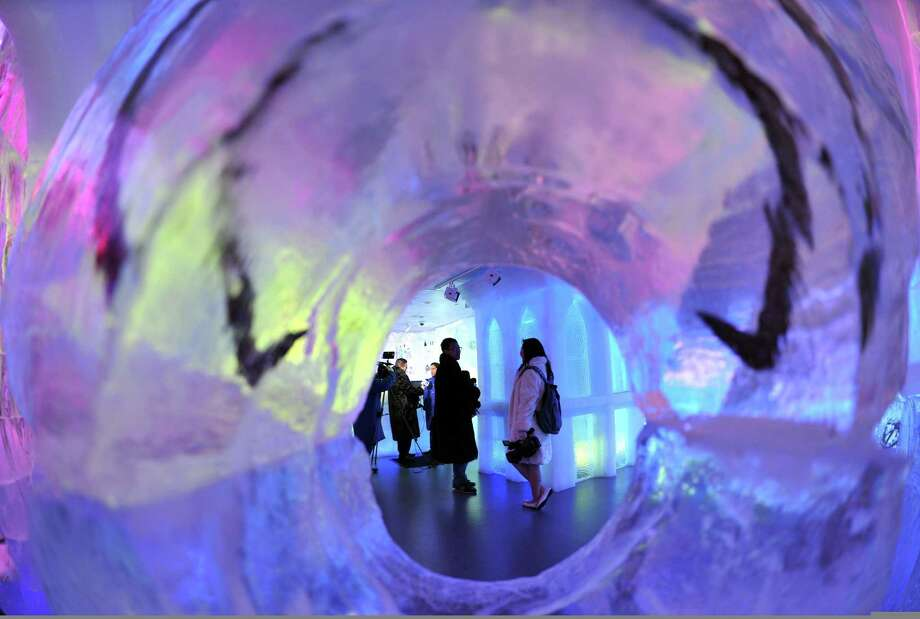 People seen through an ice scupture in the Minus 5 Ice Bar during a preview at the New York Hilton Midtown Hotel July 9, 2013 in New York. The bar is constructed of 90 tons of ice and is kept at a temperature of -5 degrees C (23 degrees F). Guests are given parkas, gloves and hats and for an additional fee, fur coats. Designs in the wall and around the bar are carved by ice sculptor Peter Slavin.  TOPSHOTS/AFP PHOTO/Stan HONDASTAN HONDA/AFP/Getty Images ORG XMIT: 173340087 Photo: STAN HONDA, Getty / AFP ImageForum