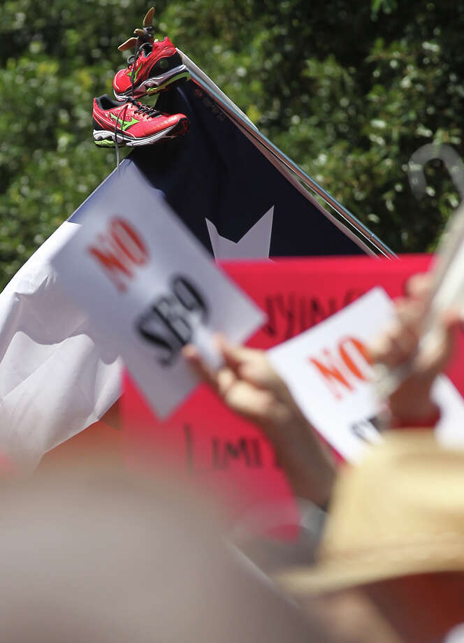 A pair of Mizuno sneakers are place a top a flag at the Stand Up With Texas Women Rally at State Capitol before the start of  the second special session, Monday, July 1, 2013. The anti-abortion legislation rally drew thousands of supporters. The sneakers were similar to the ones used by Senator Wendy Davis during her Texas Senate filibuster last Tuesday. Photo: Jerry Lara, San Antonio Express-News / ©2013 San Antonio Express-News