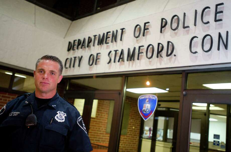 Stamford Police Officer Seth O'Brien poses for a portrait before beginning his midnight shift in Stamford, Conn., on Tuesday, July 9, 2013. O'Brien has been named Stamford's Police Officer of the Year. Photo: Lindsay Perry / Stamford Advocate