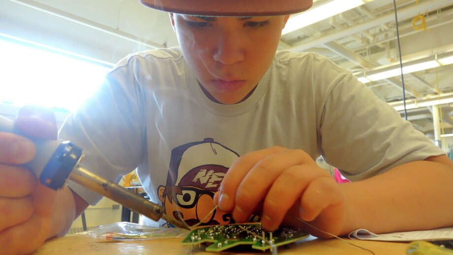 Carlos Molina, 15, solders a circuit board as he. builds an escape robot during a summer school class at Greenwich High School in Greenwich, Conn., July 10, 2013. Escape robots are all-terrain vehicles that use infrared light to sense obstacles and adjust their course accordingly. Students learn to solder points on a circuit board for resistors, oscillators and diodes, they work with gear boxes and electromagnetic motors in the process of construction. Photo: Keelin Daly / Stamford Advocate Freelance