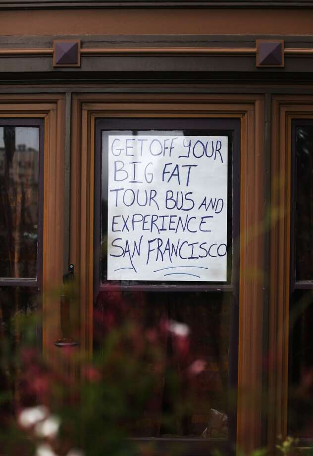 A sign protesting tour bus use of Alamo Square is seen in a lower window of the Westerfeld House on July 2, 2013 in San Francisco, Calif.