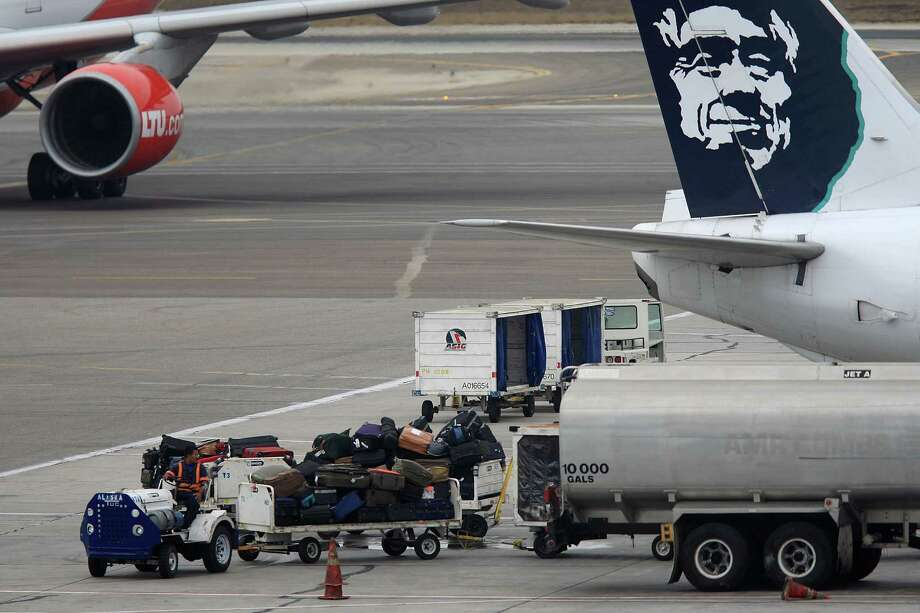 Seattle-based Alaska Airlines just announced plans to raise its fee for checking a suitcase from $20 to $25.The change, for tickets purchased on or after Oct. 30, would bring Alaska in line with most major airlines. Additional bags will cost $75 (currently the second and third bags are also $20).On the bright side, Alaska is boosting its payoff if bags aren't at baggage claim within 20 minutes of the plane parking at the gate from $20 toward a future flight or 2,000 frequent flier miles to $25 or 2,500 miles.Also, Alaska plans to increase its fee to change tickets from $75 online or $100 by phone to $125. There's no fee for changes made 60 or more days in advance.Click on to see how these fees compare to those of other North American airlines. The fees given are for the cheapest airfare options on domestic flights. Photo: David McNew, Getty Images / 2008 Getty Images