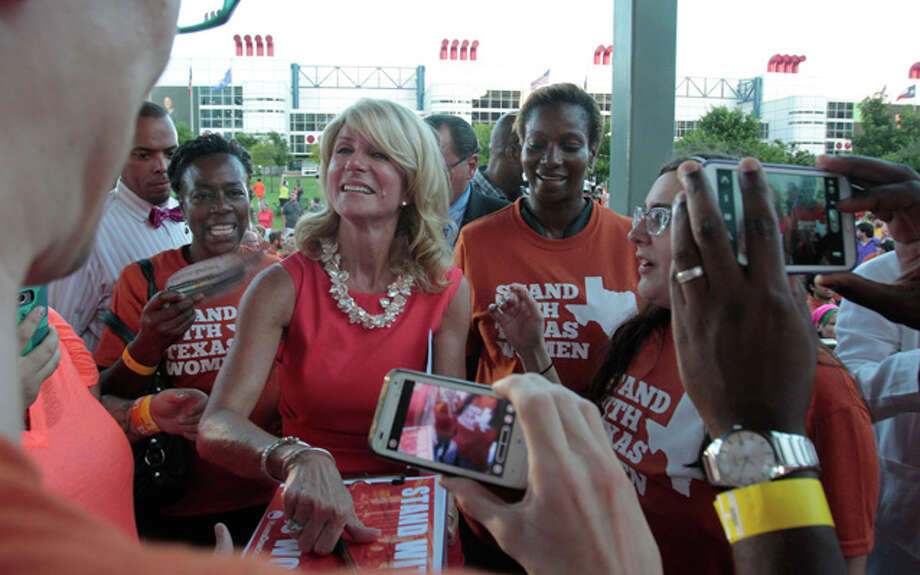 State Sen. Wendy Davis, center, signs autographs and takes photos with the crowd during the Planned Parenthood Action Fund's Stand with Texas Women Rally at Discovery Green in Houston, Texas. The Rally highlighted the abortion restriction bill, House Bill 2 being Pushed in Austin Tuesday, July 9, 2013, in Houston. (AP Photo/Houston Chronicle, Billy Smith II) Photo: Billy Smith II, ASSOCIATED PRESS / 2013 HOUSTON CHRONICLE2013