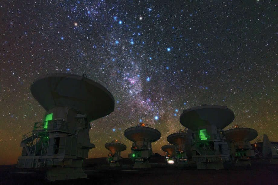 """No. 24 - """"ESO Photo Ambassador Babak Tafreshi snapped this remarkable image of the antennas of the Atacama Large Millimeter/submillimeter Array (ALMA), set against the splendour of the Milky Way. The richness of the sky in this picture attests to the unsurpassed conditions for astronomy on the 5000-metre-high Chajnantor plateau in Chile's Atacama region.  This view shows the constellations of Carina (The Keel) and Vela (The Sails). The dark, wispy dust clouds of the Milky Way streak from middle top left to middle bottom right. The bright orange star in the upper left is Suhail in Vela, while the similarly orange star in the upper middle is Avior, in Carina. Of the three bright blue stars that form an """"L"""" near these stars, the left two belong to Vela, and the right one to Carina. And exactly in the centre of the image below these stars gleams the pink glow of the Carina Nebula (eso1208),"""" according to the European Space Observatory. Photo: ESO"""
