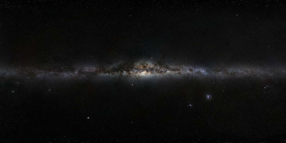 """No. 20 - """"This magnificent 360-degree panoramic image, covering the entire southern and northern celestial sphere, reveals the cosmic landscape that surrounds our tiny blue planet. This gorgeous starscape serves as the first of three extremely high-resolution images featured in the GigaGalaxy Zoom project, launched by ESO within the framework of the International Year of Astronomy 2009 (IYA2009). The plane of our Milky Way Galaxy, which we see edge-on from our perspective on Earth, cuts a luminous swath across the image. The projection used in GigaGalaxy Zoom place the viewer in front of our Galaxy with the Galactic Plane running horizontally through the image — almost as if we were looking at the Milky Way from the outside. From this vantage point, the general components of our spiral galaxy come clearly into view, including its disc, marbled with both dark and glowing nebulae, which harbors bright, young stars, as well as the Galaxy's central bulge and its satellite galaxies. As filming extended over several months, objects from the Solar System came and went through the star fields, with bright planets such as Venus and Jupiter. For copyright reasons, we cannot provide here the full 800-million-pixel original image, which can be requested from Serge Brunier. The high resolution image provided here contains 18 million pixels,"""" according to the European Space Observatory. Photo: ESO"""