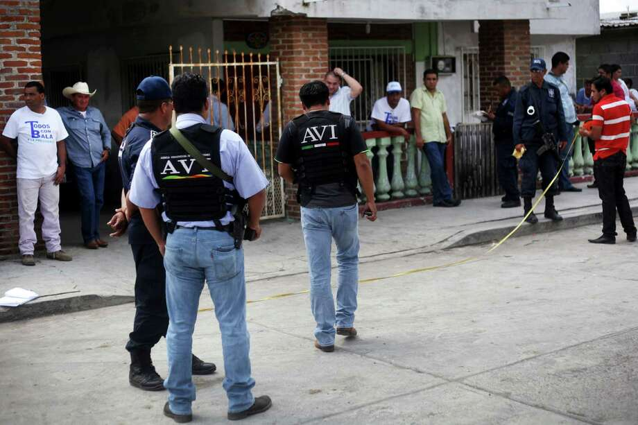 State police and forensic experts stand outside the home of mayoral candidate Carlos Triana Garcia after   gunmen opened fire on his home in Tlalixcoyan, Mexico. Prior to this week's elections in 14 states, at least eight local politicians or their family members were killed. Photo: Felix Marquez, Associated Press / AP