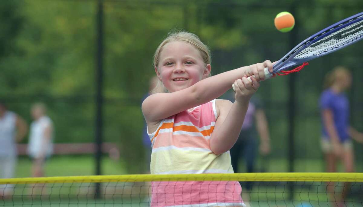 Ellie hits a ball over the net during a tennis clinic, hosted by the New Haven Open tournament, at Dickerson Park in Newtown, Conn, for Park & Recreation summer campers on Wednesday July 10, 2013. The clinic featured WTA tennis pro Melanie Oudin.