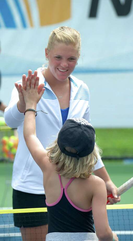 WTA tennis professional Melanie Oudin high fives a camper during a clinic she conducted at Dickerson Park in Newtown, Conn, for Park & Recreation summer campers on Wednesday July 10, 2013. The clinic was hosted by the New Haven Open. Photo: H John Voorhees III