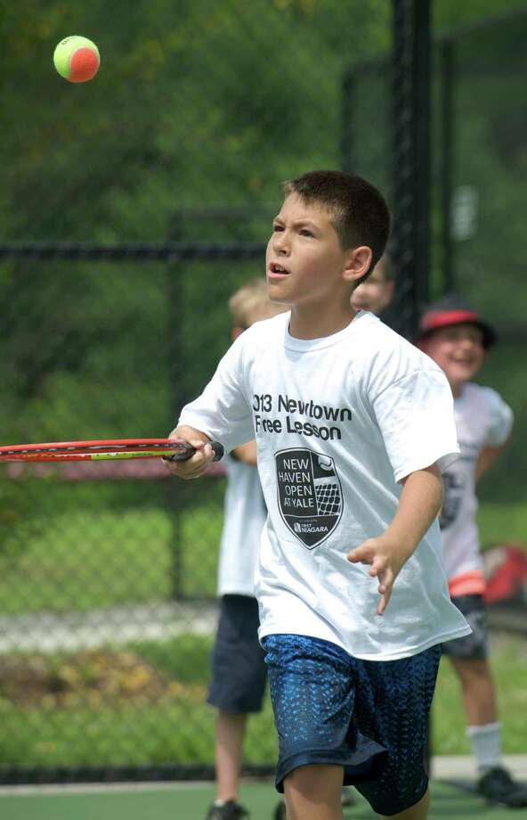 Chris bounces a ball off his racquet as part of a drill during a tennis clinic, hosted by the New Haven Open tournament, at Dickerson Park in Newtown, Conn, for Park & Recreation summer campers on Wednesday July 10, 2013. Photo: H John Voorhees III