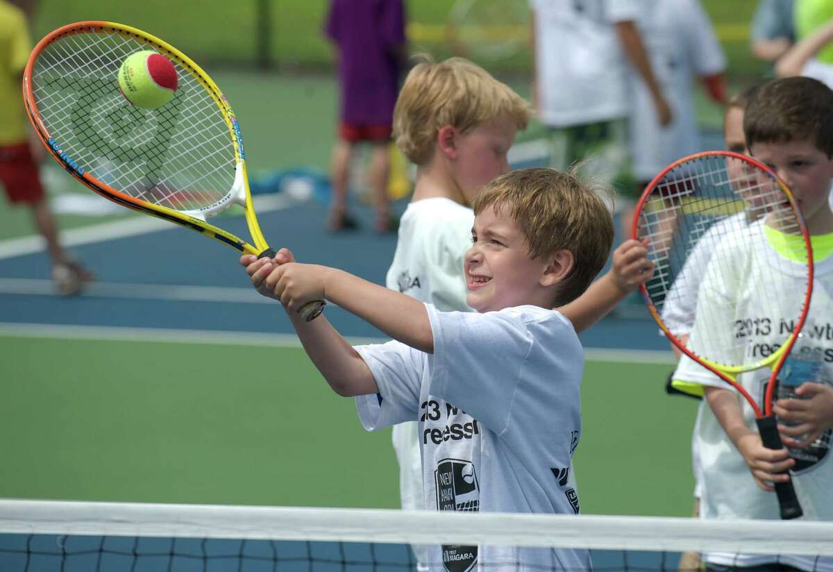 Evan hits a ball over the net during a tennis clinic, hosted by the New Haven Open tournament, at Dickerson Park in Newtown, Conn, for Newtown Park & Recreation summer campers on Wednesday July 10, 2013.