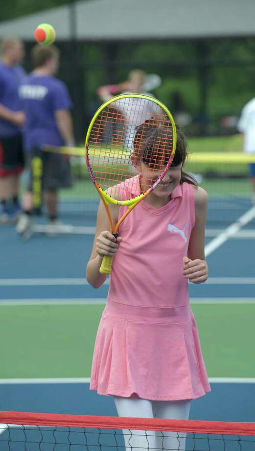 Kayleigh hits a ball over the net during a tennis clinic, hosted by the New Haven Open tournament, at Dickerson Park in Newtown, Conn, for Park & Recreation summer campers on Wednesday July 10, 2013. Photo: H John Voorhees III