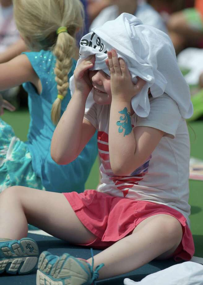 Mikayla tries to keep cool by putting a shirt over her head at a tennis clinic, hosted by the New Haven Open tournament, at Dickerson Park in Newtown, Conn, for Park & Recreation summer campers on Wednesday July 10, 2013. Photo: H John Voorhees III
