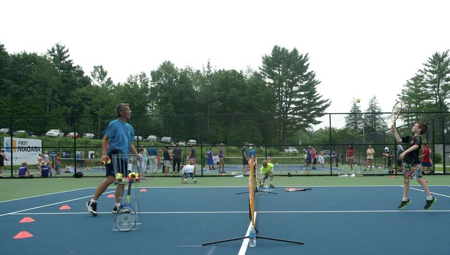 Henry Eng, a tennis pro from Southington, works with Nicholas during a clinic held  in Newtown, Conn, for  Park & Recreation summer campers on Wednesday July 10, 2013. The clinic was sponsored by the New Haven Open and featured WTA tennis pro Melanie Oudin. Photo: H John Voorhees III