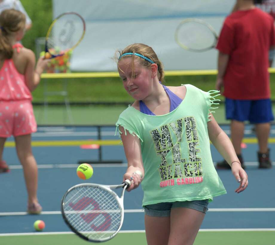 Mikayla returns a ball during a tennis clinic, hosted by the New Haven Open tournament, at Dickerson Park in Newtown, Conn, for Newtown Park & Recreation summer campers on Wednesday July 10, 2013. Photo: H John Voorhees III