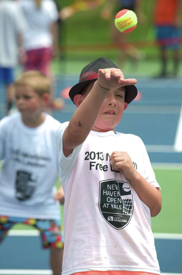 Robbie throws a ball to another camper during a  tennis clinic, hosted by the New Haven Open tournament, at Dickerson Park in Newtown, Conn, for Newtown Park & Recreation summer campers on Wednesday July 10, 2013. Photo: H John Voorhees III