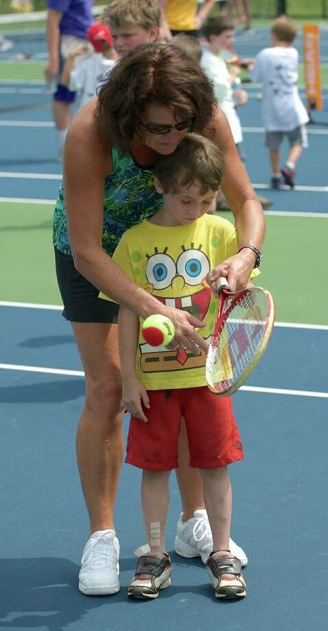 Jill Nemeth, of Newtown, shows Brian how to grip a racquet. at a tennis clinic, hosted by the New Haven Open tennis tournament, in Newtown, Conn, on Wednesday July 10, 2013. Photo: H John Voorhees III