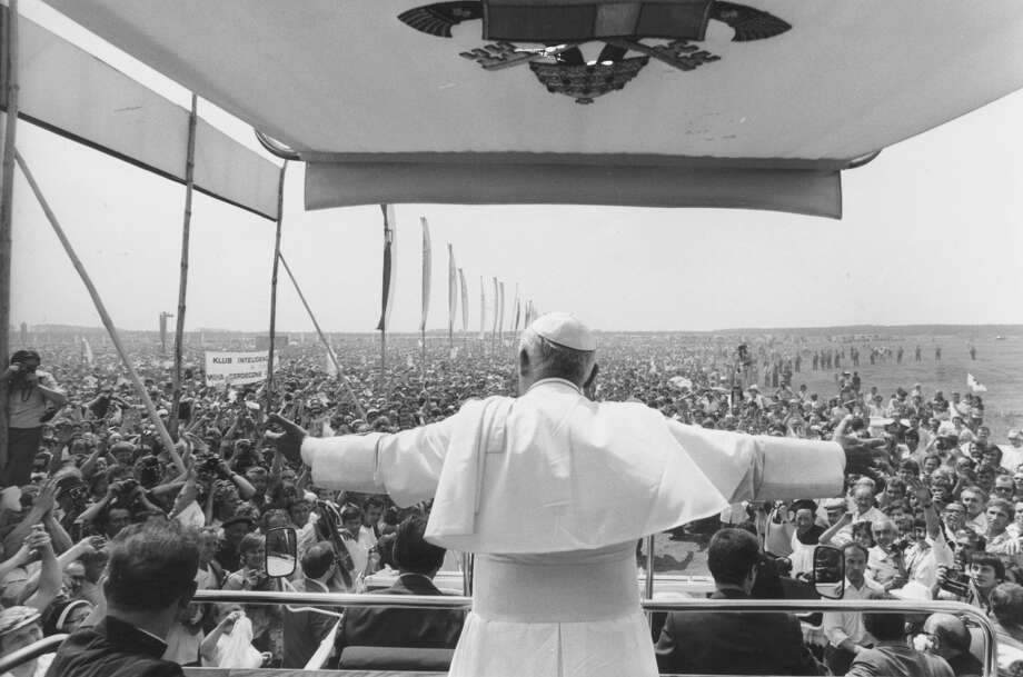 Pope John Paul II rides in the Pope-mobile with his back to the camera and his arms outstretched as a crowd looks on during an eight day visit to Poland, June 1979. (Photo by Keystone/Getty Images)