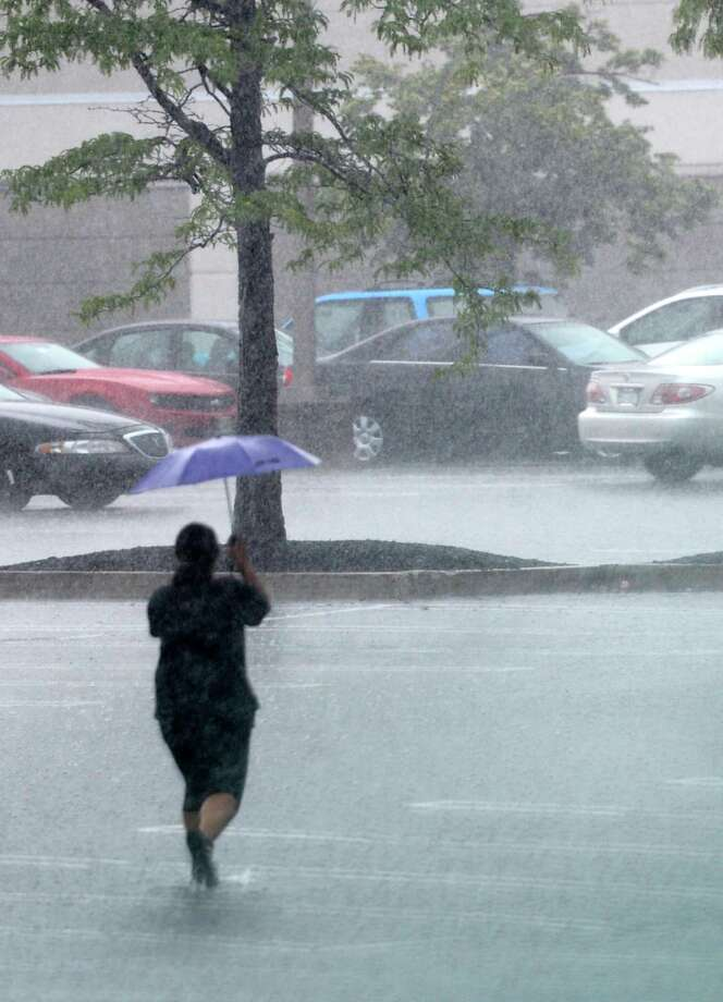 A shopper walks through heavy rain near Sears in Colonie Center parking lot Wednesday afternoon, July 10, 2013, in Colonie, N.Y. (Skip Dickstein/Times Union) Photo: SKIP DICKSTEIN