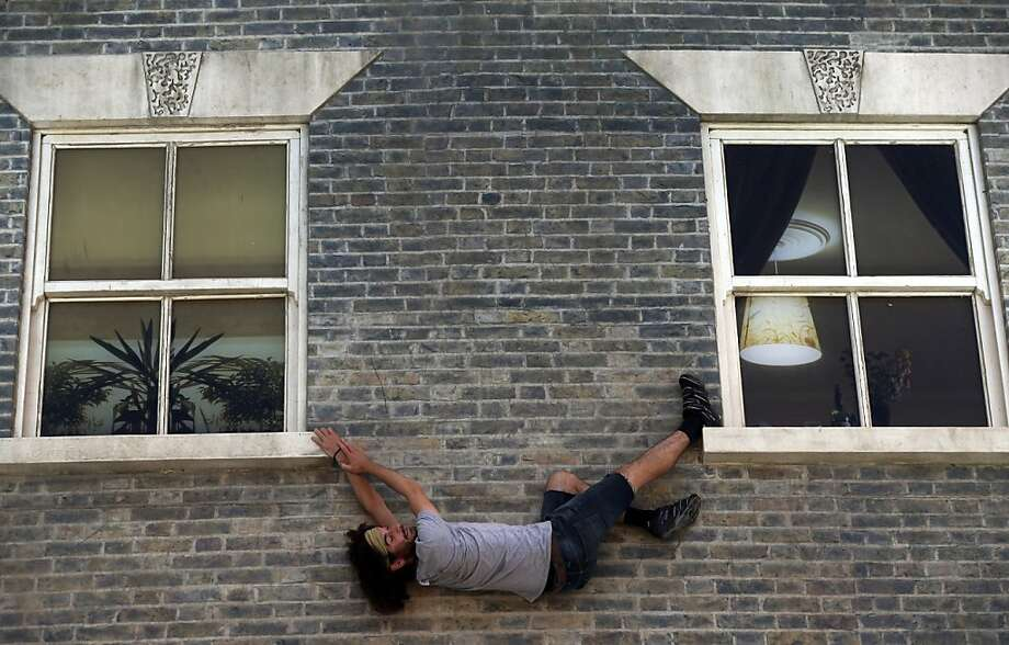 "What looks like a terrific climbing moveis actually not so impressive - the ""climber"" is lying horizontally in this 3-D illusion created by Argentine artist Leandro Erlich in east London. Resembling a theater set, the detailed facade of a Victorian terraced house - recalling those that once stood on the street - uses mirrors positioned overhead to give the impression that the bricks are part of a vertical structure. Photo: Lefteris Pitarakis, Associated Press"