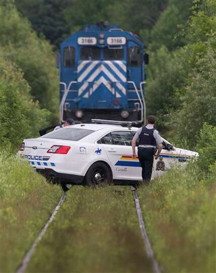 Royal Canadian Mounted Police officers guard the main locomotive involved in a July 6 fatal train de