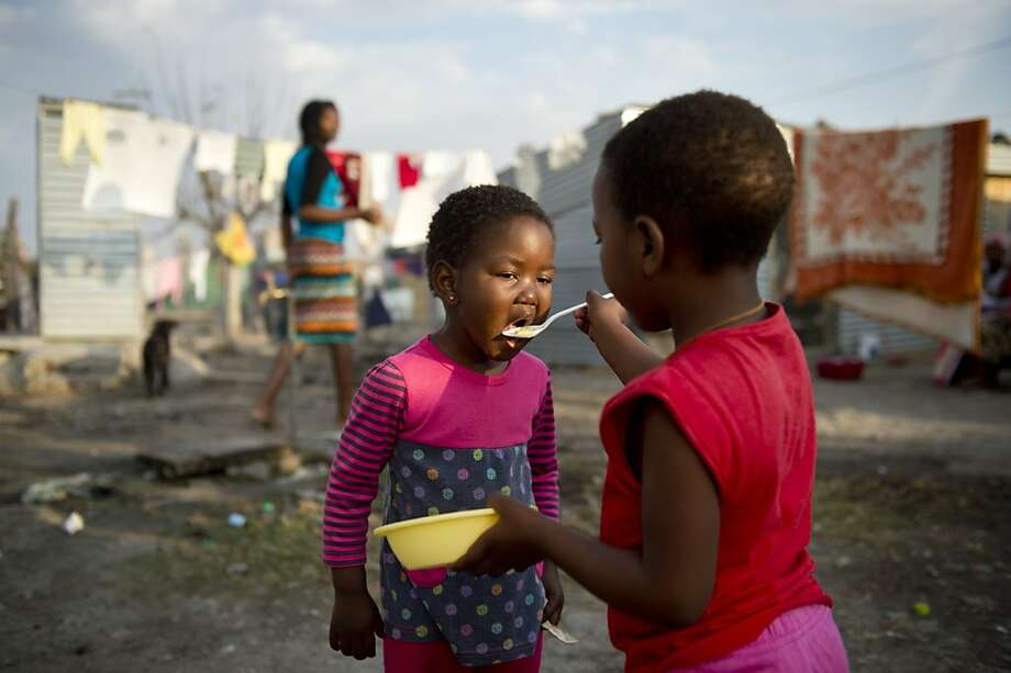 A girl feeds her sister in the Nkaneng shantytown next to a platinum mine run by the British company Lonmin in Marikana, South Africa. Last August, police at the Marikana mine opened fire on striking workers, killing 34 and injuring 78, during a strike for better wages and living conditions. Despite a small wage increase, miners still live in poverty. Photo: Odd Andersen, AFP/Getty Images