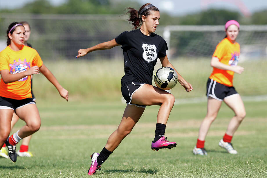 Katelyn Fouse (center) drives the ball upfield during a Lions FC '96 practice session at Lions Pride Park, 49 Manske Road, on Tuesday, July 2, 2013.  The local girls club soccer team consisting of high school players who will be seniors next fall, has qualified for the U.S. Youth Soccer National Presidents Cup July 11-14 in Auburndale, Fla.  The squad is the first in San Antonio history to advance to the four-team event.  MARVIN PFEIFFER/ mpfeiffer@express-news.net Photo: MARVIN PFEIFFER, Marvin Pfeiffer/ Express-News / Express-News 2013