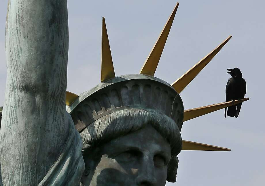 Give me your tired, your poor, your enormous crows yearning to be fed ... The bird seems to be gargantuan because Miss Liberty in Tokyo is only a scaled-down model of the real McCoy in New York Harbor. Photo: Shizuo Kambayashi, Associated Press
