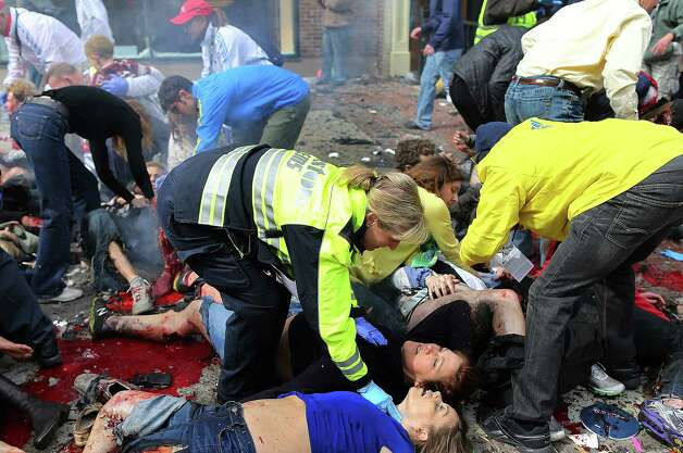 BOSTON - APRIL 15: (EDITOR'S NOTE: THIS IMAGE CONTAINS GRAPHIC CONTENT) Victims lay on the sidewalk as emergency personnel respond to the scene of the first explosion near the finish line of the Boston Marathon, April 15, 2013. (Photo by John Tlumacki/The Boston Globe via Getty Images) Photo: Boston Globe, Wire / 2013 - The Boston Globe