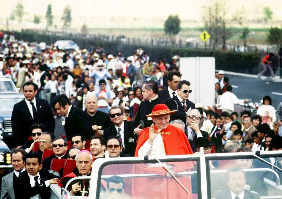 """Pope John Paul II waves from his popemobile 26 January 1979 in Mexico City at the beginning of his first Pastororal visit outside Italy to Santo Domingo, Mexico and the Bahamas, from 25 January to 01 February 1979. Background, (3rd from left, standing), US Archbishop Paul Marcinkus, head of """"Instituto per de Religione."""""""