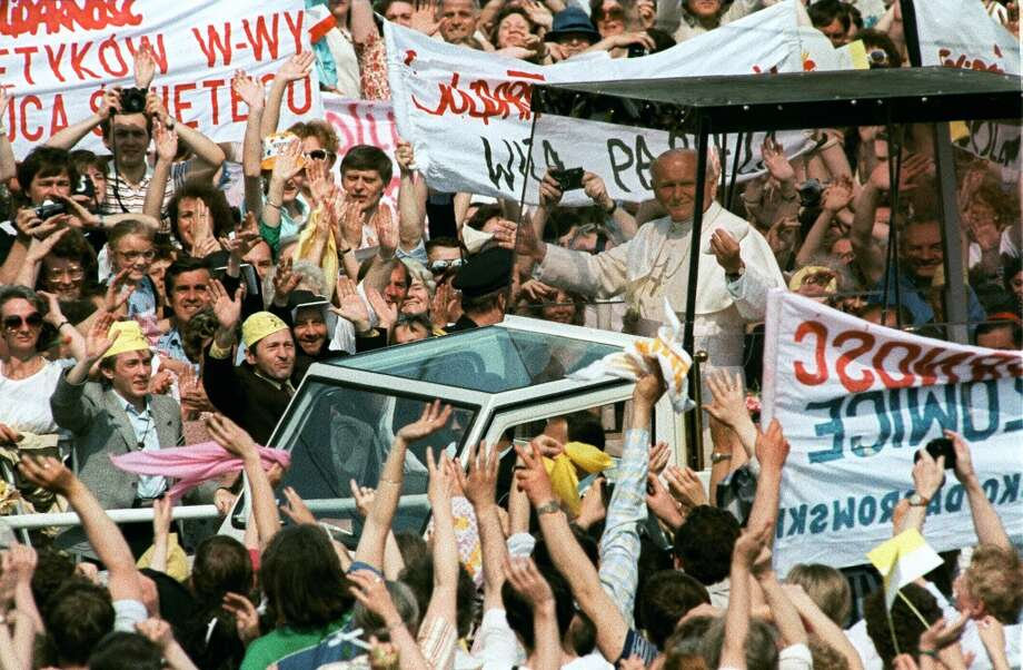 Pope John Paul II salutes from his popemobile 14 June 1987 in Warsaw cheering crowd during the last day of his third visit to his homeland.