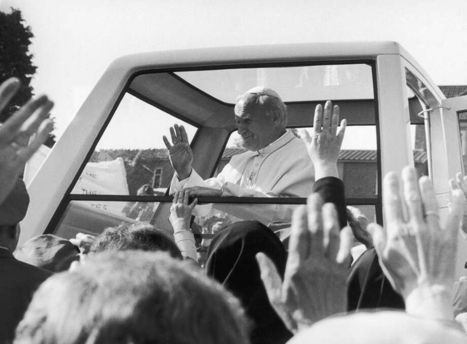 Pope John Paul II waves from the window of his 'Popemobile' during a visit to Digby Stuart Catholic College in Roehampton, London.