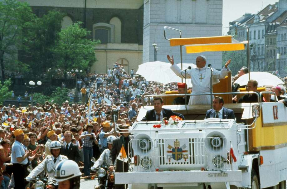 Pope John Paul II, atop APC-like Popemobile, waving to crowds gathered to watch procession through streets during papal visit.