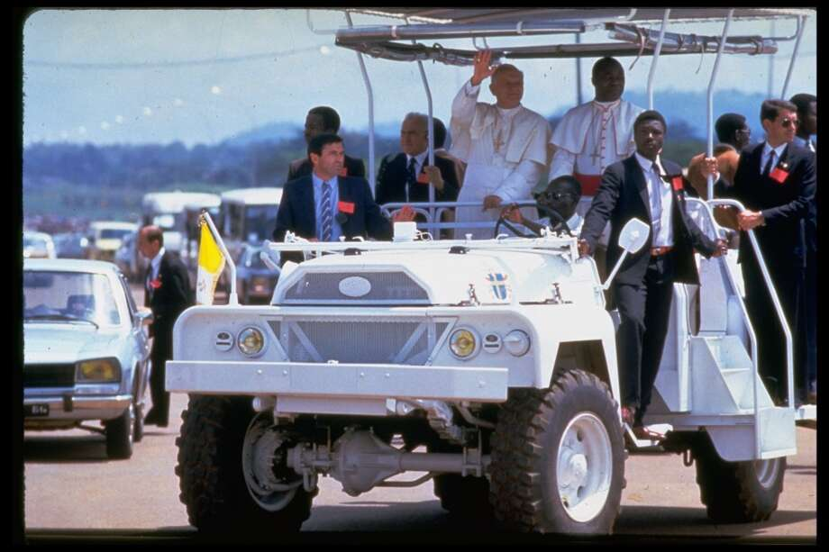 Pope John Paul II, in heavily guarded Popemobile, waving to crowds gathered to watch procession through streets during papal visit.