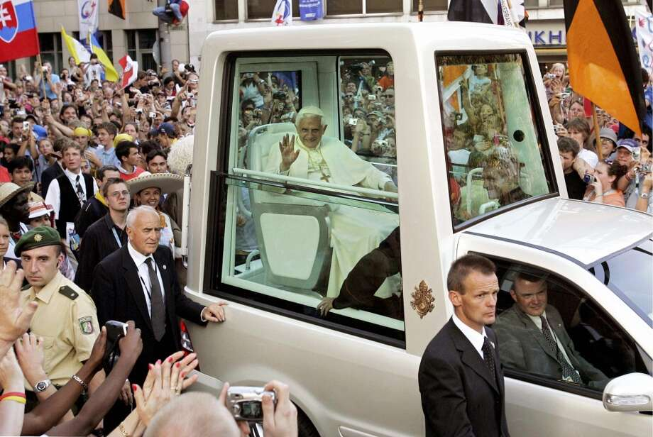 Pope Benedict XVI waves to pilgrims as he makes makes his way through the crowd in his Popemobile, 18 August 2005 in Cologne, on the first day of his groundbreaking four-day visit to his native Germany, during the Catholic World Youth Day festival. More than 400,000 young Catholics from nearly 200 countries were set to welcome the new pope to the Catholic stronghold of Cologne for the jamboree.