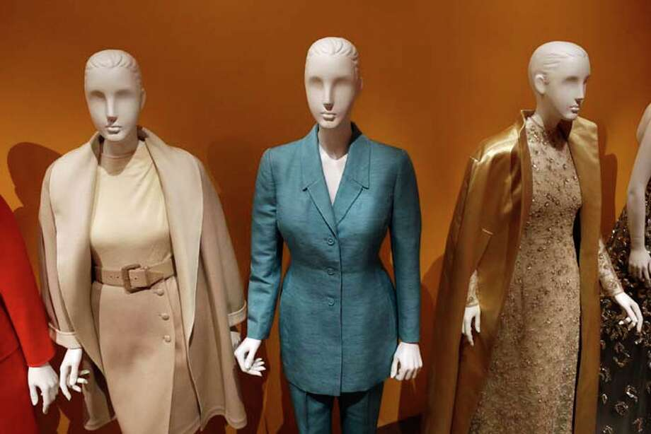 """An Oscar de la Renta pantsuit, center, worn by Former first lady Hillary Rodham Clinton, is displayed next to other creations by the designer at the Clinton Presidential Library in Little Rock, Ark., Monday, July 8, 2013. The """"Oscar de la Renta: American Icon"""" exhibit is on display at the Clinton library until Dec. 1. (AP Photo/Danny Johnston) Photo: Danny Johnston, Associated Press / AP"""