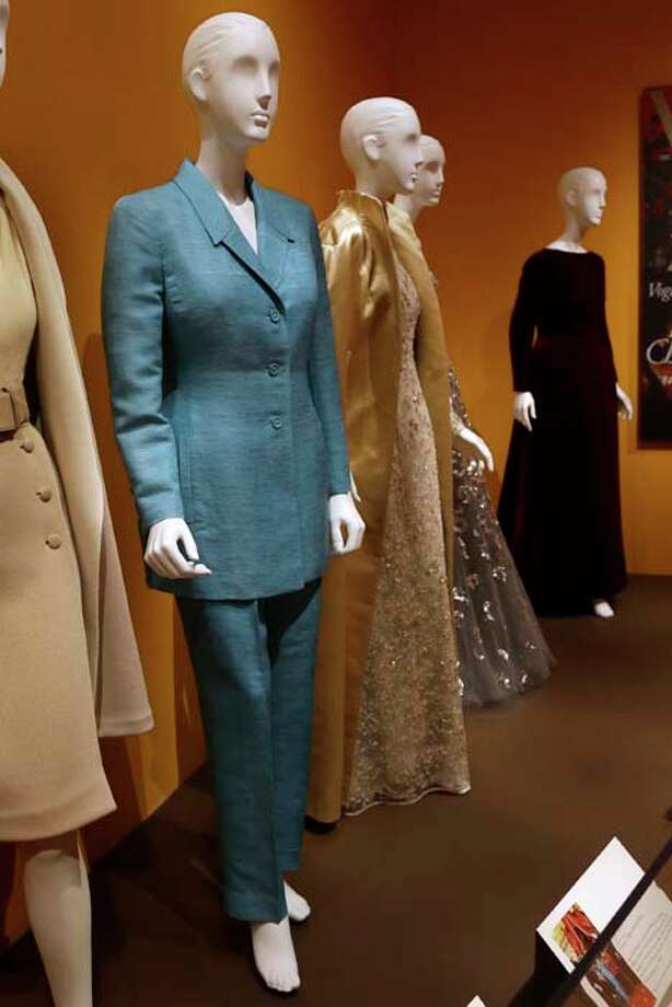 "An Oscar de la Renta pantsuit, left, worn by former first lady Hillary Rodham Clinton, is displayed next to other creations by the designer at the Clinton Presidential Library in Little Rock, Ark., Monday, July8, 2013. The ""Oscar de la Renta: American Icon"" exhibit is on display at the Clinton library until Dec. 1. (AP Photo/Danny Johnston) Photo: Danny Johnston, Associated Press / AP"
