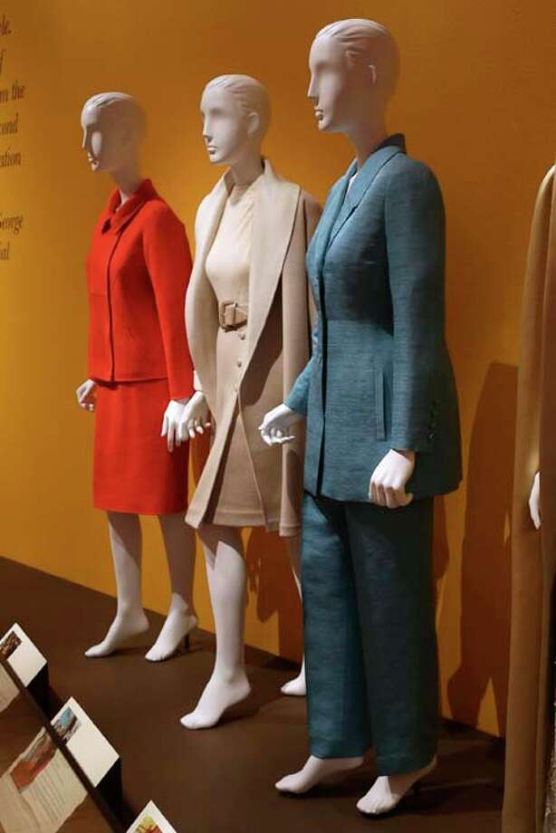 "An Oscar de la Renta pantsuit worn by former first lady Hillary Rodham Clinton, right, is displayed next to  de la Renta dresses worn by Nancy Regan, center, and Laura Bush at the Clinton Presidential Library in Little Rock, Ark., Monday, July 8, 2013. The ""Oscar de la Renta: American Icon"" exhibit is on display at the Clinton library until Dec. 1. (AP Photo/Danny Johnston) Photo: Danny Johnston, Associated Press / AP"