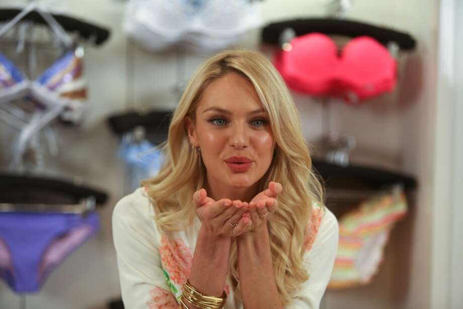 Supermodel Candice Swanepoel blows a kiss during a brief appearance for the news media.
